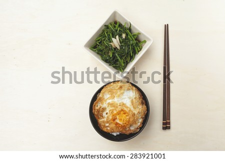 Fried vegetable and rice with crispy fried egg with space on wood table background - stock photo