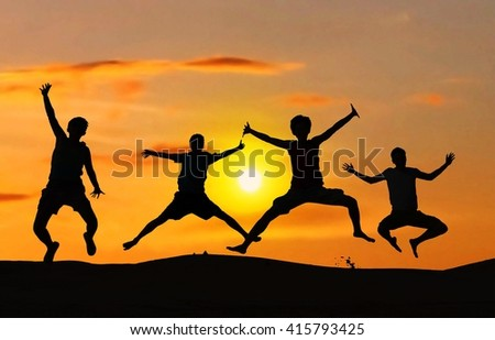 Friend group jumping in a desert with sunset. Freedom concept.