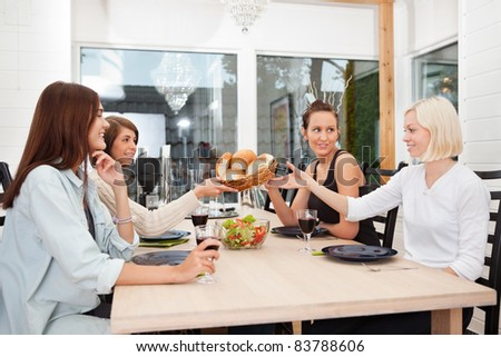 Friend passing basket filled with buns at dining table - stock photo