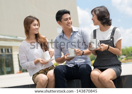 Friend's team talking and drinking coffee outdoors - stock photo