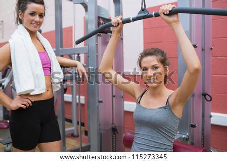 Friend stands beside woman using weights machine in gym