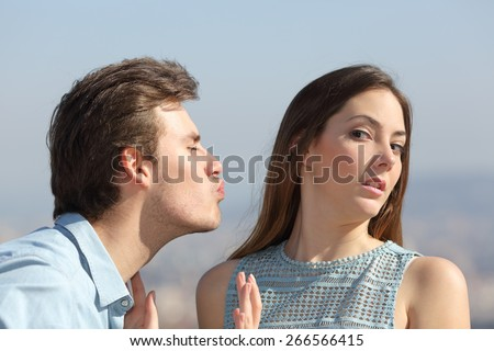 Friend zone concept with a man trying to kiss a woman and she rejecting him - stock photo