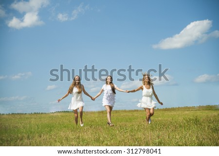 Friendgirl concept. Three smiling girls run at green grass at background of blue sky with clouds. 3 young adult woman walk on summer field Empty space for inscription or objects