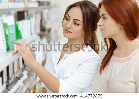 Friendly advice. Professional pharmacist helping her customer at the local drugstore.  - stock photo