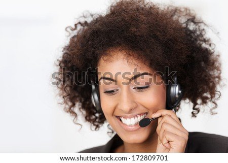 Friendly African American call centre operator wearing a headset in her curly hair smiling warmly as she listens to the conversation while helping a client - stock photo
