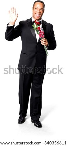 Friendly African man with short black hair in evening outfit holding flowers - Isolated