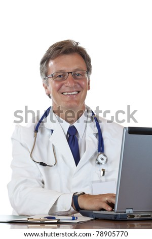 Friendly aged doctor types recipe on laptop and smiles . Isolated on white background.