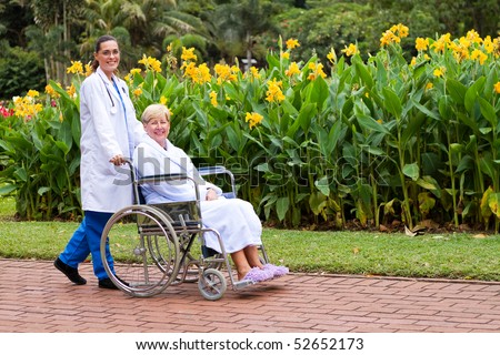 friendly and caring female doctor push senior patient on wheelchair outdoors for a walk