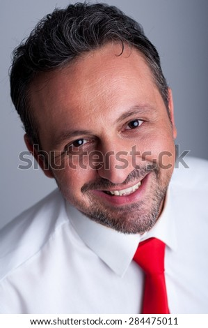 Friendly and reliable smiling politician face portrait with red tie or necktie