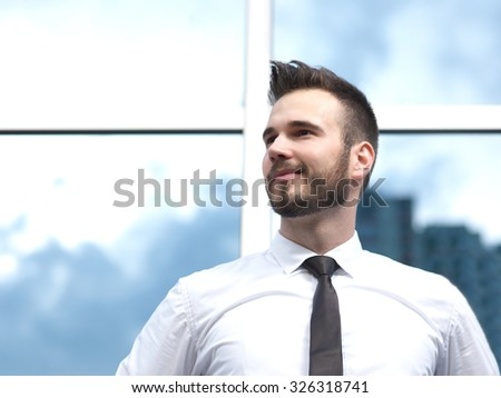 Friendly and smiling handsome businessman in front of building,