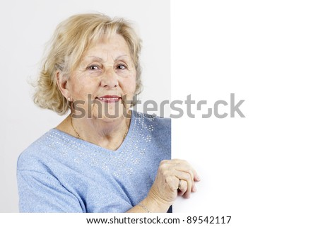 Friendly and smiling senior woman holding a blank white sign or placard ready for advertisement or information. - stock photo