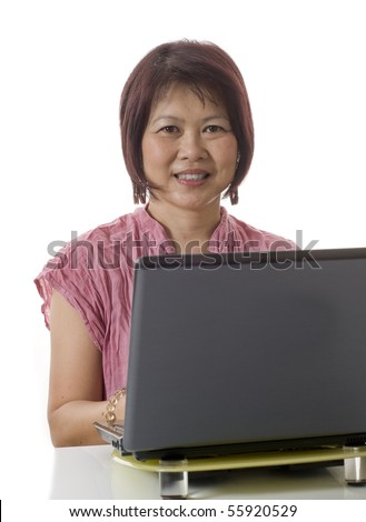 Friendly Asian woman sitting at desk with computer isolated on white - stock photo