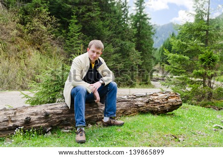 Friendly attractive man sitting on a tree trunk alongside a gravel mountain road winding through a lush green valley