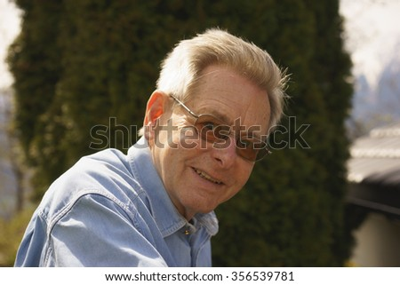 Friendly attractive senior man in glasses outdoors in his garden turning to smile at the camera, head and shoulders portrait - stock photo