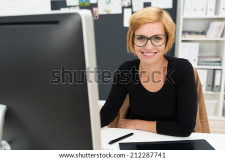 Friendly attractive young businesswoman sitting at her desk in the office smiling at the camera past her computer monitor - stock photo