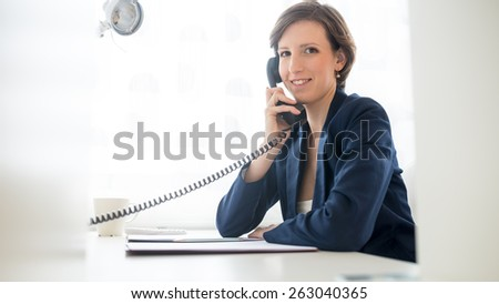 Friendly attractive young businesswoman talking on the telephone as she sits at her desk in the office turning to smile at the camera. - stock photo