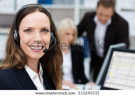 Friendly attractive young call centre operator or member of the client services team wearing a headset turning to give the camera a lovely warm smile - stock photo