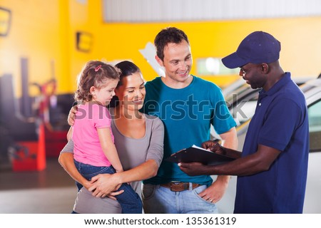 friendly auto mechanic talking to young family in garage - stock photo