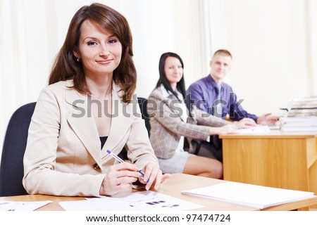 Friendly bank consultant sitting at the table - stock photo