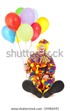 Friendly birthday clown with balloons, sitting with his big feet to the camera.  Isolated on white. - stock photo