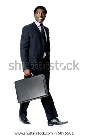 friendly black businessman walking with his briefcase smiling and happy - stock photo
