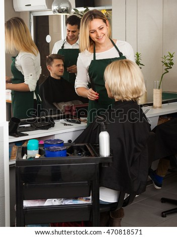 Friendly blonde girl cuts hair of mature woman at salon