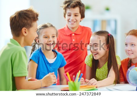 Friendly boys and girls talking and laughing at break in school - stock photo