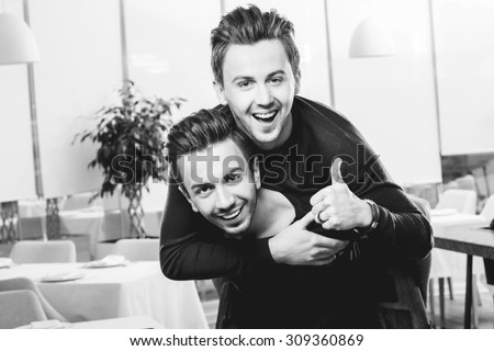 Friendly brothers twins having fun riding piggyback in the white home or restaurant interior. Family relationship between two brothers. Black and white photo - stock photo