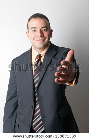 Friendly business man greeting the viewer and extending his hand out for a handshake. - stock photo