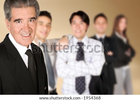 friendly business man smiling with his colleagues blurred in the background - stock photo