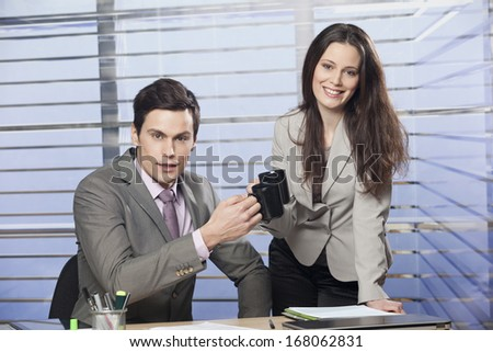 Friendly business partners drinking coffee in office - stock photo