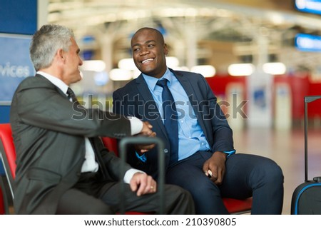 friendly business travellers handshaking at airport - stock photo