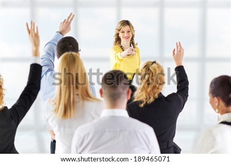 Friendly business woman explaining plan of work and answering the question. The team is listening and asking the questions. - stock photo