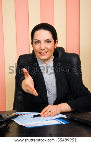 Friendly business woman sitting at desk in office and giving handshake or welcome sign hand