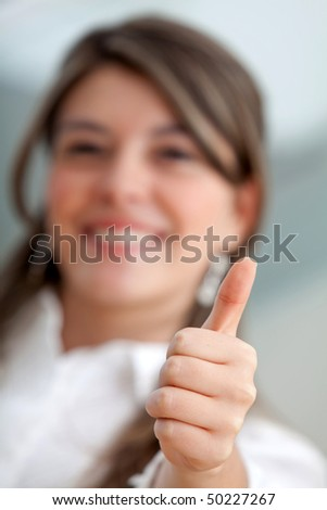 Friendly business woman smiling with thumb up - focus on hand