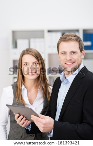 Friendly businessman and woman in an office standing holding a tablet computer and smiling at the camera - stock photo