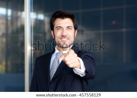 Friendly businessman pointing his finger at you