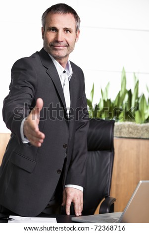 Friendly businessman standing in office behind  desk and stretching out hand for handshake,  closing a business deal or agreement. - stock photo