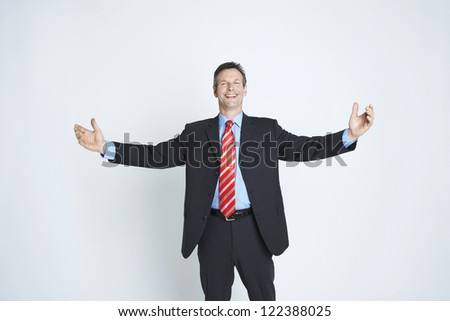 Friendly businessman standing with open arms - stock photo