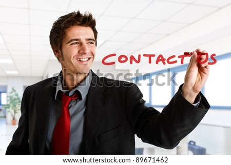 Friendly businessman writing Contact Us on the screen - stock photo