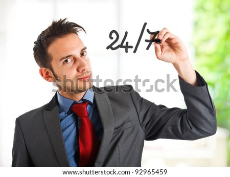 Friendly businessman writing 24/7 on the screen - stock photo