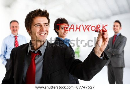 Friendly businessman writing the word Teamwork on the screen - stock photo