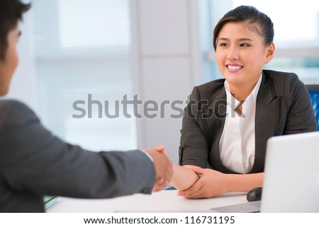 Friendly businesswoman shaking hands with a collaborator - stock photo