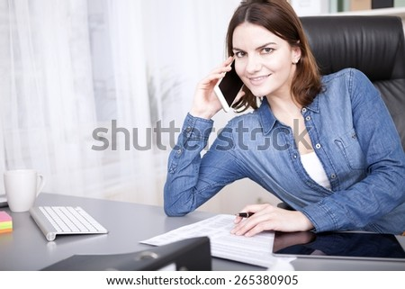 Friendly businesswoman smiling at the camera as she takes a phone call in the office while sitting working at her desk - stock photo