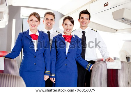Friendly cabin crew in an airplane smiling - stock photo