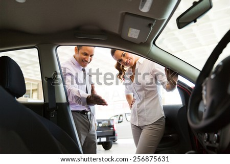 friendly car dealer showing new car to customer - stock photo