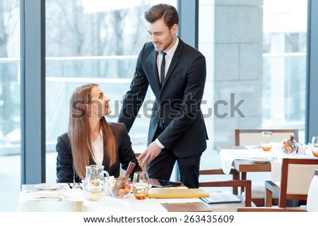 Friendly care after the colleagues. Young smiling business manager holds a chair where his female colleague is sitting so that he could help her stand up - stock photo