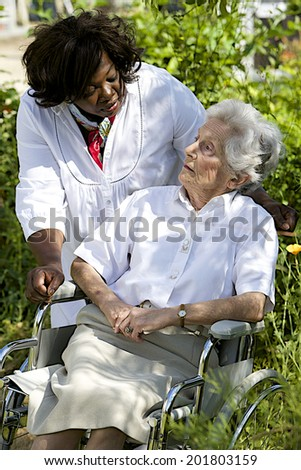 friendly care giver talking to disabled senior patient outdoor - stock photo