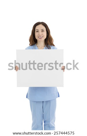 Friendly caucasian female doctor or nurse showing a white blank poster for advertisement
