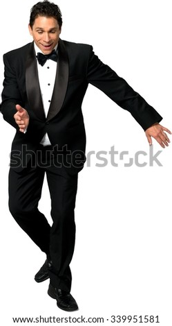 Friendly Caucasian man with short black hair in a tuxedo dancing - Isolated - stock photo